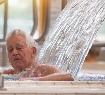 Man in spa pool with water pouring onto back   Hydrotherapy Treatments
