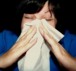 Woman blowing her nose | Using Essential Oils for Colds