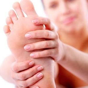 Woman doing a foot self-massage | Learn about aromatherapy and massage and related self care