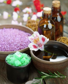 Aromatherapy supplies: two bottles, purple salts, flower floating in water | How to use essential oils